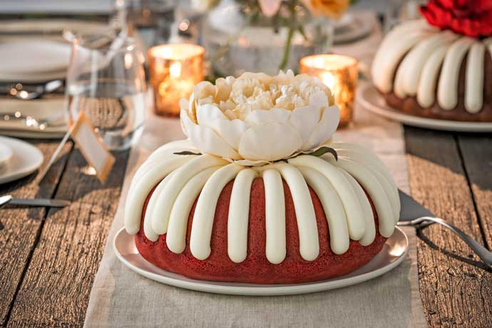 Bundt cake with a large flower decoration on a wooden table with candles.