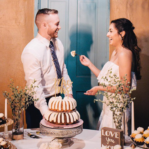 Couple on their wedding day, feeding each other from a 2-tiered, 2-flavor bundt cake