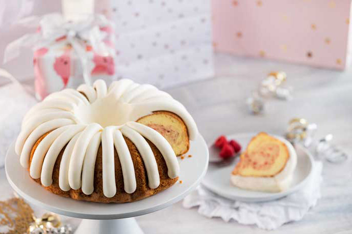Bundt cake on a white pedestal, with a slice cut out and placed on a plate